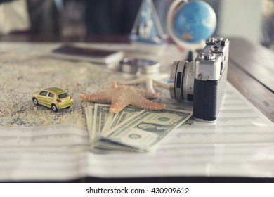 map, compass, passport, banknote money, globe, camera, car ship and starfish figurine on wooden table for use as traveling concept (vintage tone and selected focus)
