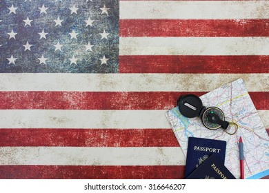 Map, compass and passports on vintage American flag canvas background