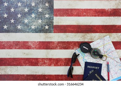 Map, compass, passports and sunglasses on vintage American flag canvas background