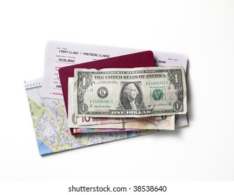Map, flight ticket, passport and money on a white surface.