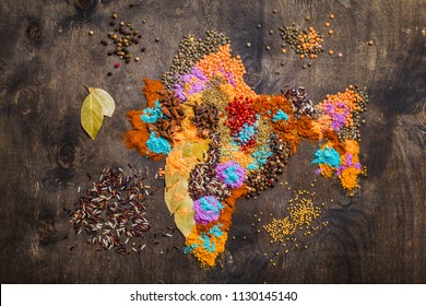 Map of India made from different traditional Indian spices, rice, lentils and Holi colours powder on dark wooden background, top view. Seasonings and ingredients for cooking Indian food, concept