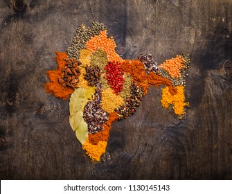Map of India made from different traditional Indian spices, rice, lentils on dark wooden background, top view. Seasonings and ingredients for cooking Indian food, concept