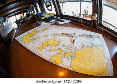 A map of the islands within Komodo National Park, Indonesia, is spread in a ship's wheelhouse. This region, part of the Coral Triangle, is a popular destination for scuba divers and snorkelers.