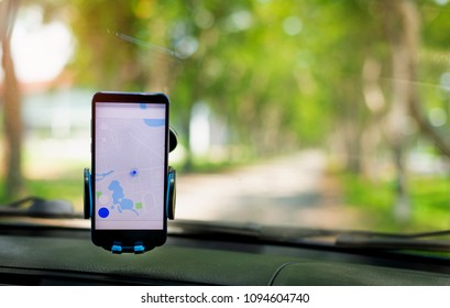 The map on the phone in the background of the dashboard and country side . Black mobile phone with map  navigation fixed in the mounting. copy space.