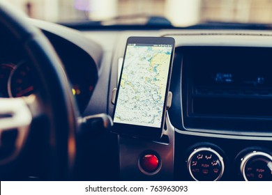 The map on the phone in the background of the dashboard. Black mobile phone with map gps navigation fixed in the mounting. Vintage style photo