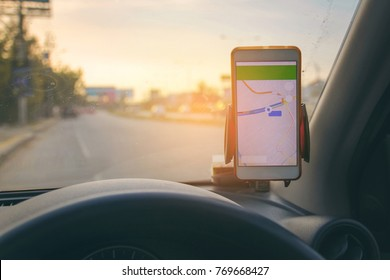 The map on the phone in the background of the dashboard and street . White mobile phone with map gps navigation fixed in the mounting. copy space.