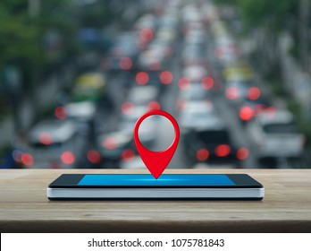 Map pin location button on modern smart phone screen on wooden table over blur of rush hour with cars and road, Map pointer navigation concept