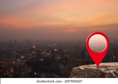 Map pin location button on rock over blur of cityscape on warm light sundown, Map pointer navigation concept