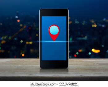 Map pin location button on modern smart phone screen on wooden table over blur colorful night light of city tower, Map pointer navigation concept