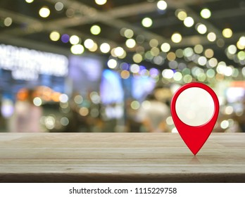 Map pin location button on wooden table over blur light and shadow of shopping mall, Map pointer navigation concept