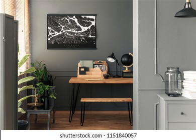 Map poster hanging on the wall in real photo of open space room interior with hairpin bench, desk with lamp, black globe, wooden organizer and tea cup