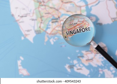 Map of Singapore consulted with a magnifying glass highlighting the name of the city