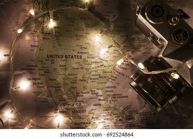 Map of United States Of America, travel concept with old vintage camera with christmas lights around