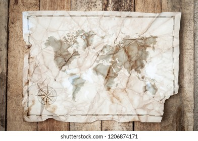 Map of the world shape spots on Vintage Crumpled paper texture on wooden table. Retro map of the Earth
