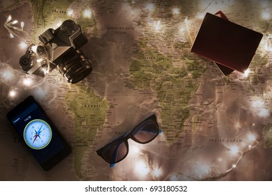 Map of the world, travel concept with old vintage camera, passports, compass, sun shades and money with christmas lights around