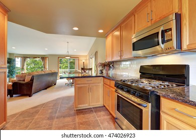 Maple kitchen cabinetry, granite counter top, steel appliances and tile floor. Kitchen room interior and living room behind. Northwest, USA