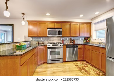 Maple kitchen cabinets with steel appliances and granite tops. Practical design with tile back splash trim