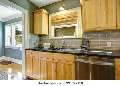 Maple kitchen cabinets with tile back splash trim, built-in dishwasher and sink