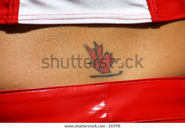 Maple leaf tattoo on the small of the back of a girl wearing PVC pants and red & white top