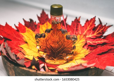 Maple syrup bottle in red maple tree leaves for tourist gift souvenir. Canada grade A amber sweet liquid from Quebec sugar shack.