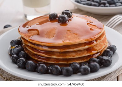 Maple syrup is flowing down the pancakes, and blueberries serve the decoration of this meal. The result of an American recipe for your breakfast.