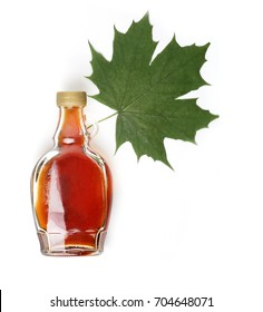 maple syrup and maple leaf on white background
