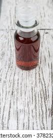 Maple vinegar in glass vial over wooden background
