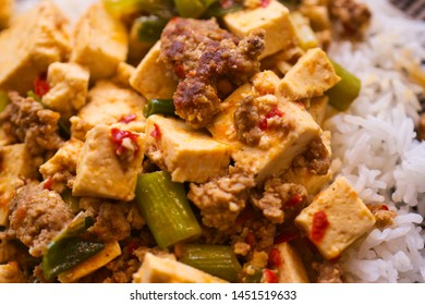 Mapo Doufu also known as Mapu Tofu, a spicy Asian dish made from minced meat and tofu cubes with spring onions and lots of chili, close up
