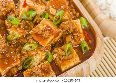 Mapo Tofu - Tofu and minced pork cooked with chili bean paste, fermented black beans, chili oil and Szechuan peppers, garnished with spring onions. Served with white steamed rice. Close up.
