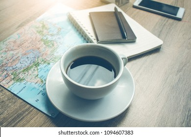 Maps and hot coffee and a passport and a pen and notebook and mobile on the wooden table