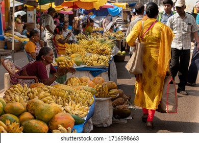 Mapusa, Goa, India. February 07, 2020. An unidentified woman sells yellow bananas and an unidentified woman in a yeallow sari passes by her on Mapusa Friday market, Goa
