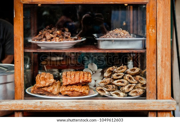 MAR 1, 2018 Uthaithani, Thailand : Ingredients, crispy pork, fried fish at Thai local street food shop at evening food market