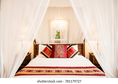 Mar 11, 2014 BANGKOK, Thailand  : Vintage Colonial style wooden four poster bed with curtain, colourful pillows