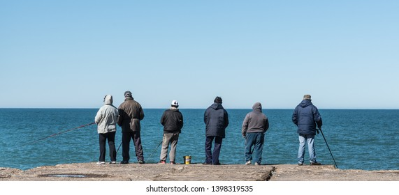 Mar del Plata, Argentina - August 22 2016: Fishermen with fishing rod, they try to fish not for fun but to eat.