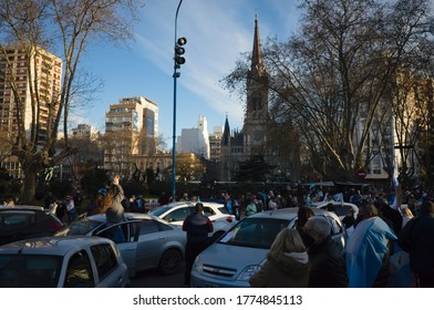 Mar del Plata, Argentina - July, 2020: People  celebrate Independence Day of Argentina. People waving national flags in San Martin park against Mar del Plata cathedral catholic church