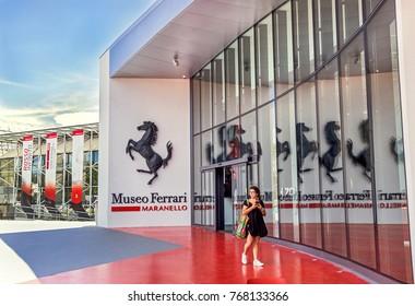 Maranello, Italy - July 26, 2017: Girl near main entrance to famous, popular Ferrari museum (Enzo Ferrari) of sport, race cars and f1.  Blue sky background. Vacation, travel, transportation concept.