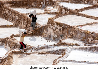 MARAS, PERU - APRIL 30, 2012 : Workers carry bags of salt collected from the Maras salt evaporation ponds. The ponds are located in the Sacred Valley of the Incas, some 40 kilometres north of Cusco.