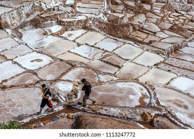 MARAS, PERU - APRIL 30, 2012 : Workers walk along the  edge of the Maras salt evaporation ponds. The ponds are located in the Sacred Valley of the Incas, some 40 kilometres north of Cusco.