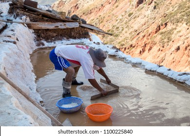 Maras, Peru - October 11, 2015: Man working in a salt evaporation pond at the Maras salt mines