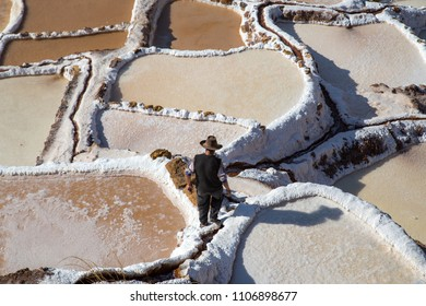Maras, Peru - October 11, 2015: Man walking in between salt evaporation ponds at the Maras salt mines