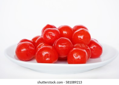 Maraschino cherries on a white plate isolated on white background