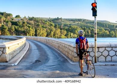 MARATHON, GREECE- JUNE 6, 2012: Cyclist waiting at the traffic light to cross the Marathon dam