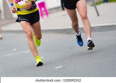 Marathon race. Closeup of the feet of runners. Muscle work