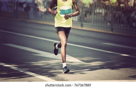 marathon runner legs running on city road