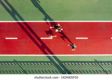 marathon runners with dog. Sport life style. Active couple on red and green bridge. Aerial drone top view