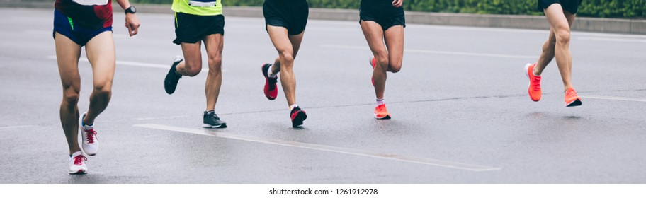 Marathon runners legs running on city road