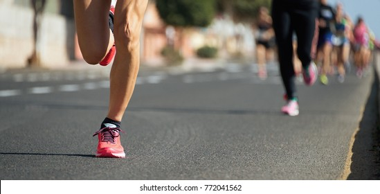 Marathon runners running on city road,detail on legs