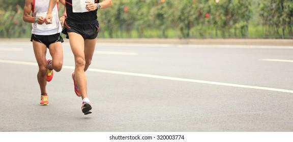 Marathon runners running race, people on city road