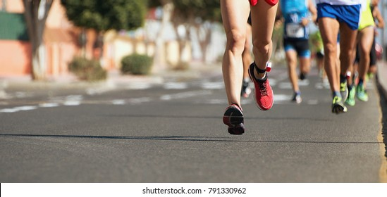 Marathon running in the light of evening,running on city road detail on legs.Copy space