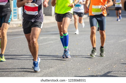 Marathon running race, group of runners on city roads, detail on legs